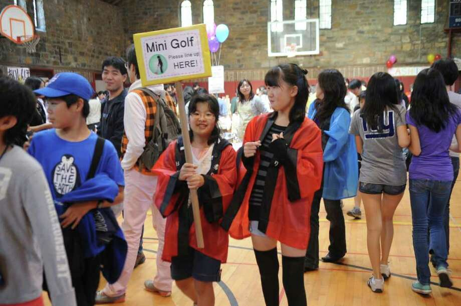 Mayi Ikushima, 13, carrying a Mini Golf advertising and Kaori Yamauchi, 13, at the Greenwich Japanese School Parent Teacher Association's Bunka Festival at the school on Sunday, Oct. 2, 2011. Photo: Helen Neafsey / Greenwich Time