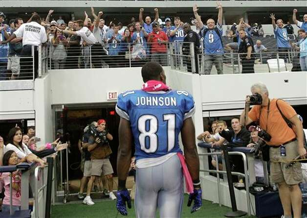 Detroit Lions wide receiver Calvin Johnson walks off the field as fans cheer following the Lions' NFL football game against the Dallas Cowboys on Sunday, Oct. 2, 2011, in Arlington, Texas. Johnson scored two touchdowns in the 34-30 Lions win. Photo: Tony Gutierrez, AP / AP