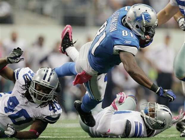 Detroit Lions wide receiver Calvin Johnson is tackled by Dallas Cowboys defensive back Danny McCray, left, and cornerback Terence Newman, right during the second half of an NFL football game Sunday, Oct. 2, 2011, in Arlington, Texas. The Cowboys won 34-30. Photo: Tony Gutierrez, AP / AP