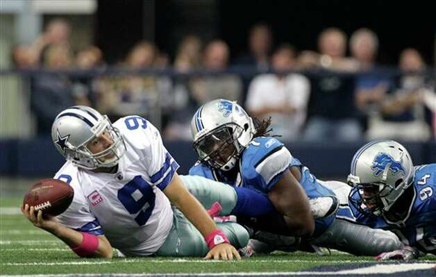 Detroit Lions defensive end Willie Young , right206 brings down Dallas Cowboys' Tony Romo (9) in the final minutes of the second half of an NFL football game Sunday, Oct. 2, 2011, in Arlington, Texas. The Lions won 34-30. Photo: Tony Gutierrez, AP / AP