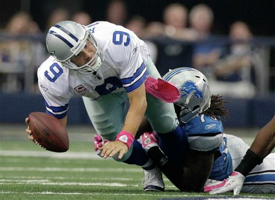 Detroit Lions defensive end Willie Young, right, brings down Dallas Cowboys quarterback Tony Romo (9) in the final minutes of an NFL football game Sunday, Oct. 2, 2011, in Arlington, Texas. The Lions won 34-30. Photo: Tony Gutierrez, AP / AP