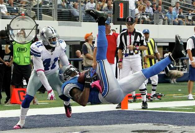 Detroit Lions wide receiver Calvin Johnson makes a 2-yard touchdown reception as Dallas Cowboys cornerback Terence Newman defends during the second half of an NFL football game Sunday, Oct. 2, 2011, in Arlington, Texas. Cowboys won 34-30. Photo: LM Otero, AP / AP