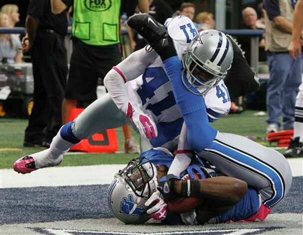 Detroit Lions wide receiver Calvin Johnson makes a two-yard touchdown as Dallas Cowboys cornerback Terence Newman defends during the second half of an NFL football game Sunday, Oct. 2, 2011, in Arlington, Texas. Cowboys won 34-30. Photo: LM Otero, AP / AP