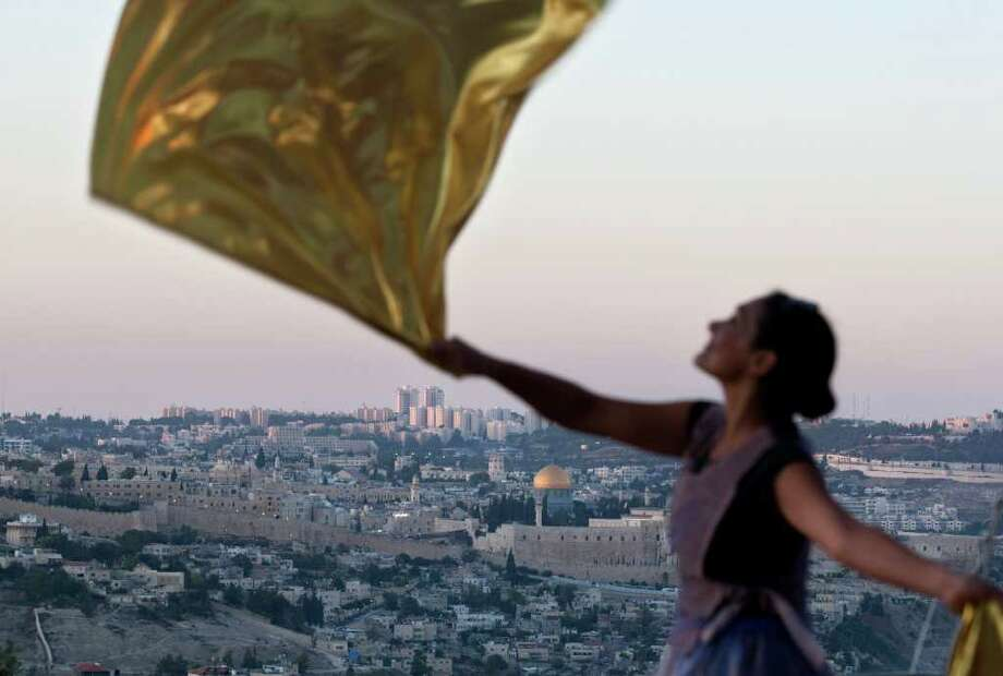 SEBASTIAN SCHEINER: ASSOCIATED PRESS SPIRITED MESSAGE: A Christian worshipper dances Sunday during a prayer for peace in Jerusalem. Mediators have called for a peace deal between Palestinians and Israel in a year. Photo: Sebastian Scheiner / AP
