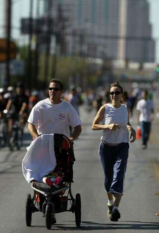 Eric Swiger pushes his six-month-old daughter Lillian Swiger while jogging with his wife Pauline Swiger down Broadway Sunday October 2, 2011 during San Antonio's first SiClovia event. The city and the YMCA have partnered to organize the free festival which encorages people to get outside and exercise. JOHN DAVENPORT/jdavenport@express-news.net Photo: SAN ANTONIO EXPRESS-NEWS