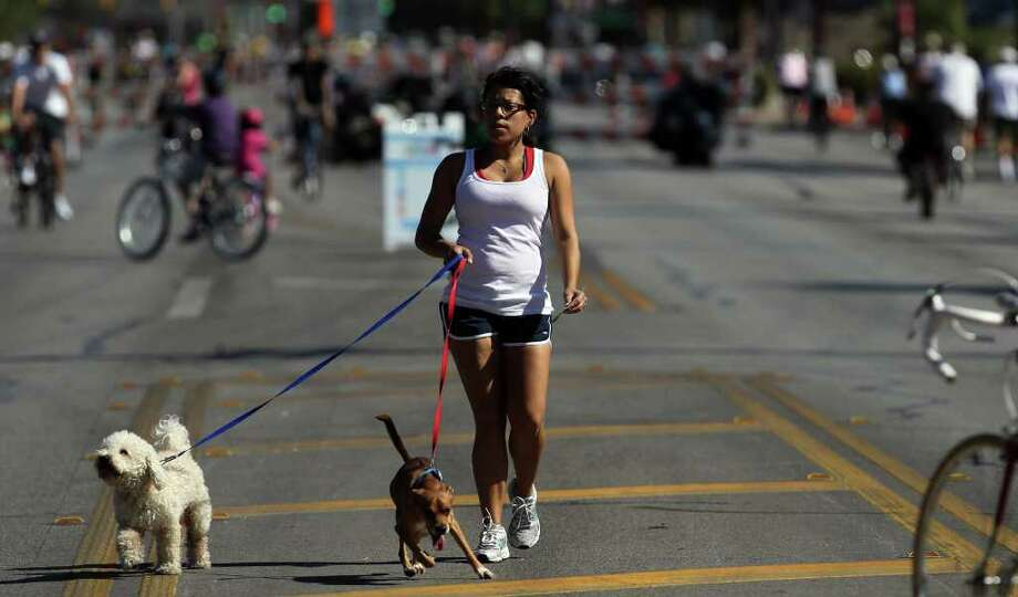 April Deleon walks her dogs down the middle of Broadway near the intersection of Mulberry Sunday October 2, 2011 during San Antonio's first SiClovia event. Two miles of Broadway were closed to motorists during the event, turning the street into a recreation area to encourage people to get out and exercise. JOHN DAVENPORT/jdavenport@express-news.net / SAN ANTONIO EXPRESS-NEWS (Photo can be sold to the public)
