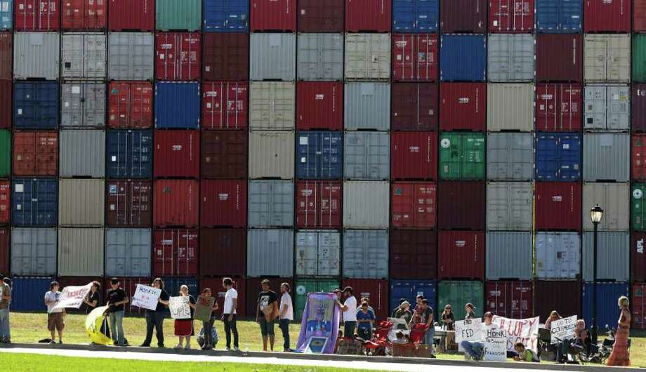 ORLIN WAGNER : ASSOCIATED PRESS MESSAGE IN ART: Demonstrators stand in front of a 65-foot-high structure by artist John Salvest that has created a buzz in Kansas City. The piece, made up of 117 cargo and storage containers, is across the street from the Federal Reserve Bank of Kansas City. Photo: Orlin Wagner / AP