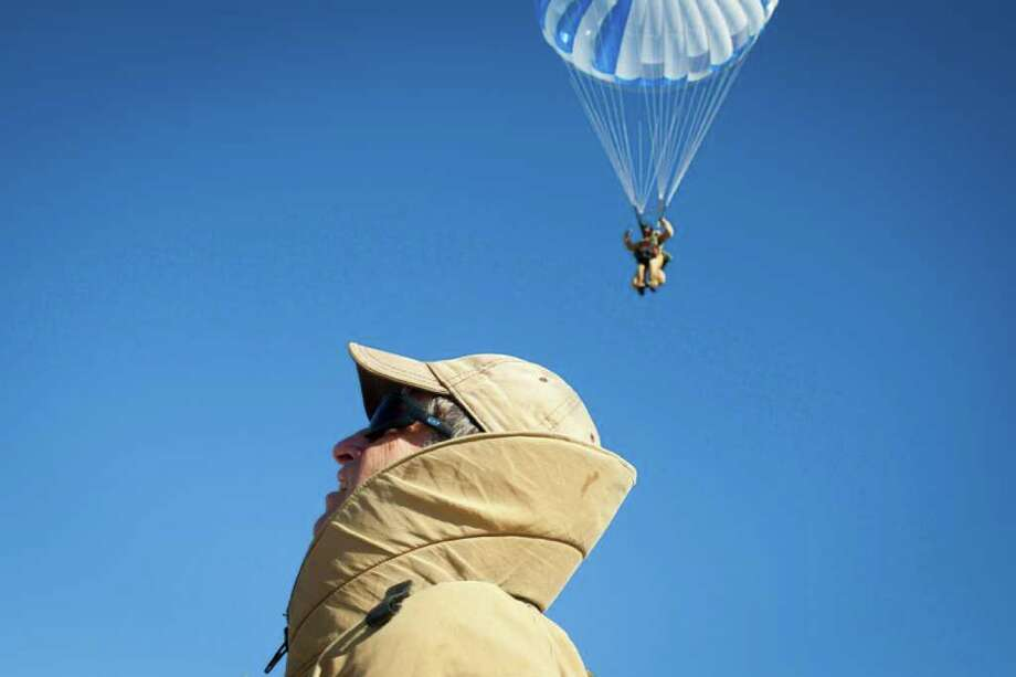MATTHEW RYAN WILLIAMS : NEW YORK TIMES OUT OF BLUE: Dale Longanecker, a smokejumper for the U.S. Forest Service, watches colleagues land after his practice jump near Winthrop, Wash., last week. Longanecker's feat of 896 jumps, 362 of which were into fires, is a record that the service says may never be broken. Photo: MATTHEW RYAN WILLIAMS / NYTNS
