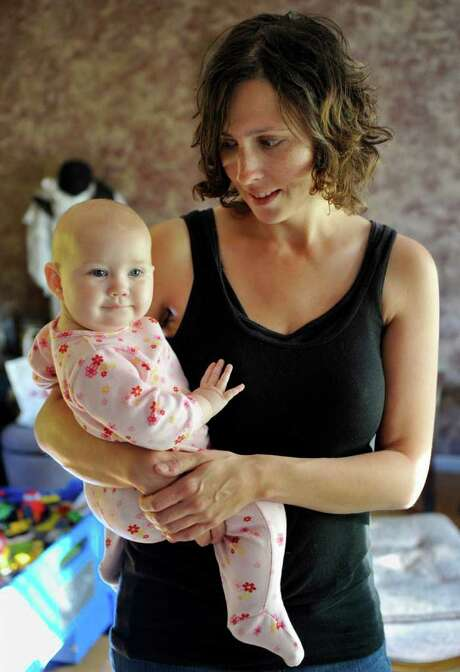 In this Sept. 29, 2011 photo, Kandace O'Neill poses with her 7-month-old daughter, in Lakeville, Minn. O'Neill's views on child vaccinations are shared by many parents who don't follow federal vaccine advice. Her 5-year-old son has had no vaccinations since he turned 1 and the baby girl has received none of the recommended shots.  (AP Photo/Jim Mone) Photo: Jim Mone / AP