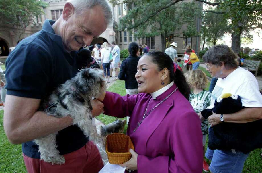 Bob Richter of Houston holding dogs, Foxy, front, and Angelita, back, with  Rev. Canon Luchy Littlejohn, right, during blessing at the annual Blessing of the Animals at Christ Church Cathedral, 1117 Texas Avenue, Sunday, Oct. 2, 2011, in Houston. The service was held in the Bishop's Courtyard in honor of St. Francis' Day.  St. Francis is the patron saint of animals and ecology.   ( Melissa Phillip / Houston Chronicle ) Photo: Melissa Phillip / © 2011 Houston Chronicle
