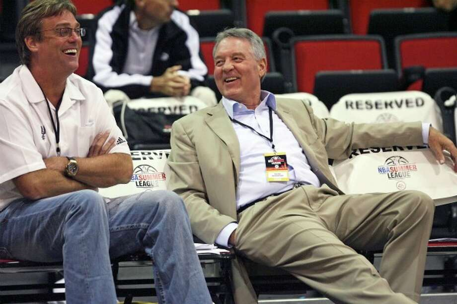 Spurs owner Peter Holt (right) and general manager R.C. Buford talk courtside before a 2009 game. Tom Reel/Express-News