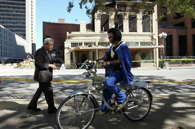 An Elvis impersonator rides by as pedestrians, bikers and others hang out at Main Plaza to watch the remains of the Wolfson Building across the street on East Commerce, Sunday, Oct. 2, 2011. The building, built in 1880, was destroyed in a four-alarm fire that started Saturday morning. Photo: Jerry Lara/glara@express-news.net / SAN ANTONIO EXPRESS-NEWS