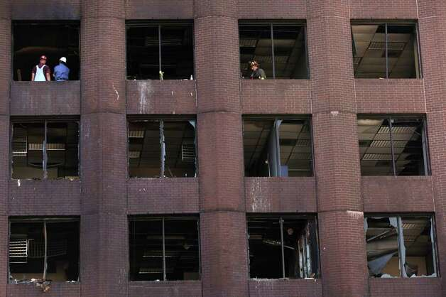 Workers and San Antonio Fire Department personnel inspect the affected floors of the Riverview Towers, Sunday, Oct. 2, 2011. The building's lower seven floors were affected by a fire that consumed the historic Wolfson Building at the corner of East Commerce and North Main early Saturday morning. Photo: Jerry Lara/glara@express-news.net / SAN ANTONIO EXPRESS-NEWS