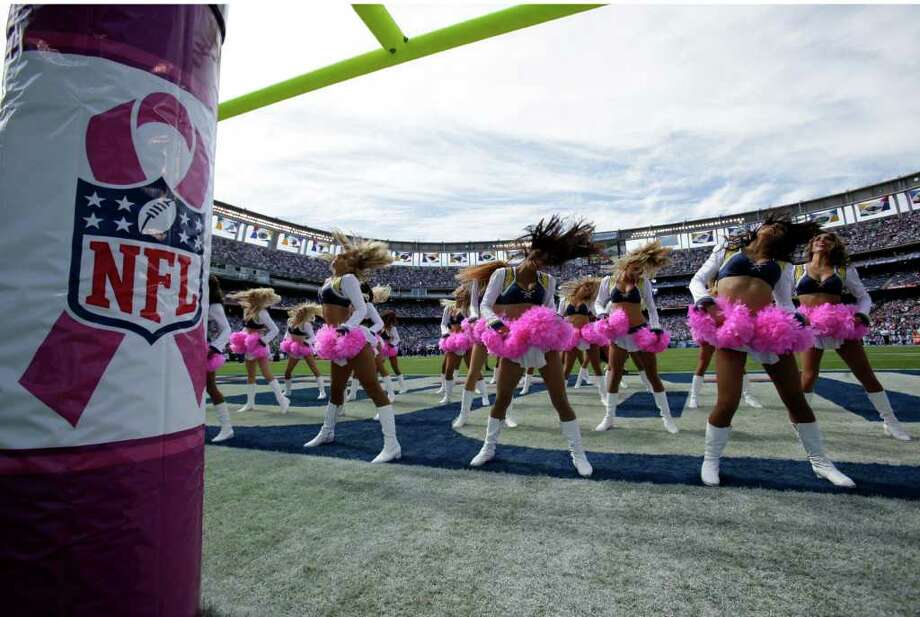 San Diego Chargers cheerleaders preform during  a NFL football game between the San Diego Chargers and the Miami Dolphins Sunday, Oct. 2, 2011, in San Diego. Signs with pink ribbon are wrapped around the goal post in honor of breast cancer awareness month. (AP Photo/Gregory Bull) Photo: Gregory Bull, Associated Press / AP