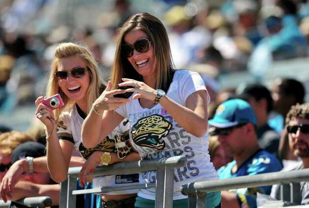 Two Jacksonville Jaguars fans take pictures of the Jacksonville Roar Cheerleaders during the first half of an NFL football game against the New Orleans Saints Sunday, Oct. 2, 2011, in Jacksonville, Fla. The Saints beat the Jaguars 23-10. (AP Photo/Stephen Morton) Photo: Stephen Morton, Associated Press / FR56856 AP