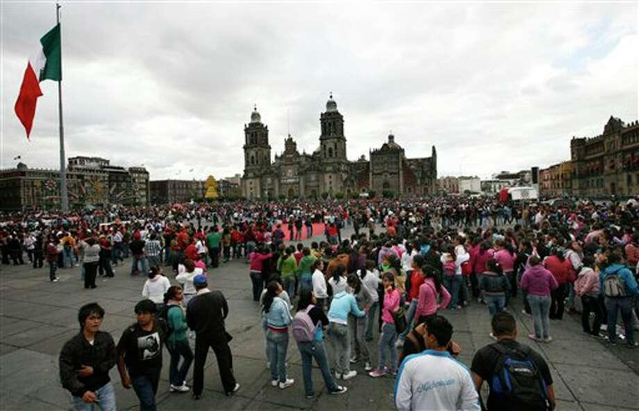 People gather during a demonstration marking the 43th anniversary of the Tlatelolco massacre at the Zocalo main square in Mexico City, Sunday Oct. 2, 2011. On Oct. 2, 1968, soldiers opened fire against a student demonstration in Mexico City's Tlatelolco Plaza just before the capital hosted the Olympics. Official reports said 25 people were killed, but human rights activists say as many as 350 may have died. (AP Photo/Marco Ugarte) Photo: Marco Ugarte, Associated Press / AP