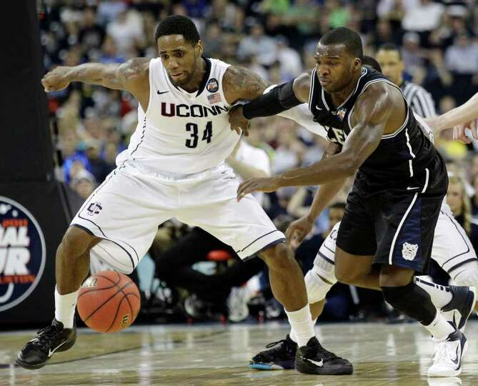 Connecticut's Alex Oriakhi and Butler's Shelvin Mack go after a loose ball cduring the second half o