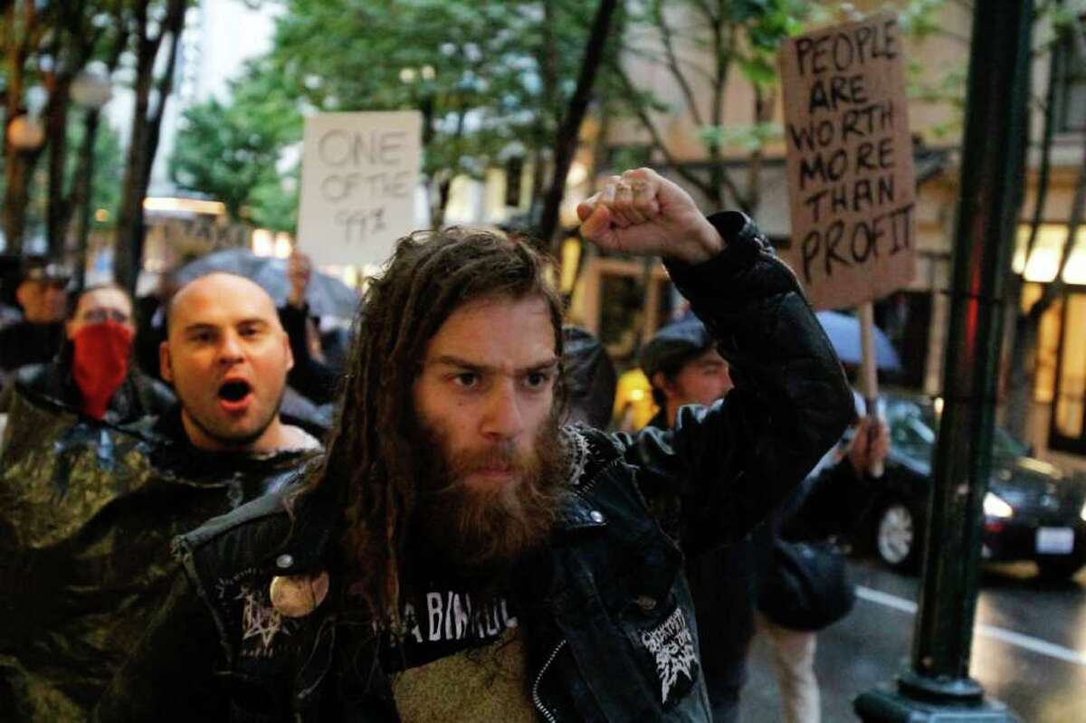Demonstrators upset with the current economic climate hold signs and yell slogans expressing their feelings towards the banks and corporations in America protest in downtown Seattle.