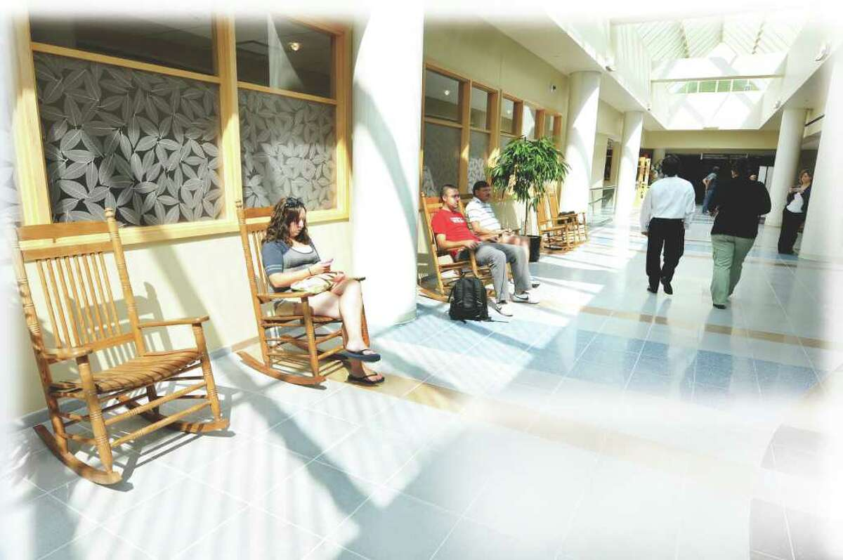 In the rocking chairs, Courtney Diefenbach of Middleburgh, left, her brother Andrew, center, and their father Gregg wait for a loved one in the new atrium on Wednesday, Sept. 14, 2011, at St. Peter's Hospital in Albany, N.Y. (Cindy Schultz / Times Union)