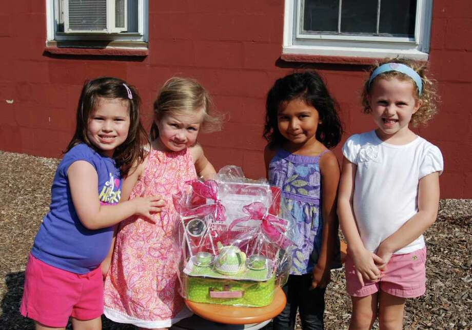 Four students in Cynthia Lorenzen, Allison Vodola and Kelly Kreppeinís Pre-K class admire the adorable American Girl Doll-themed basket they are donating to the 15th Annual Darien Family Fun Day silent auction. From left are Grace Sandoval, Samantha Veeder, Ava Gupta and Molly Fagan. Photo: Contributed Photo