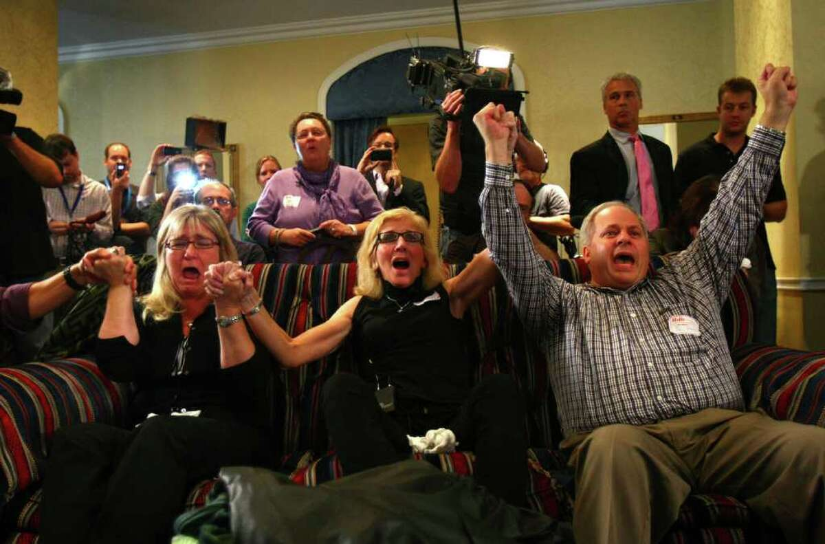 From left, supporters of Amanda Knox Kellanne Henry, Margaret Ralph, and Joe Starr, celebrate during the reading of the verdict as supporters of Amanda Knox gather on Monday at the Fairmont Olympic Hotel in Seattle. The supporters gathered to hear a verdict in the Knox murder trial in Italy.