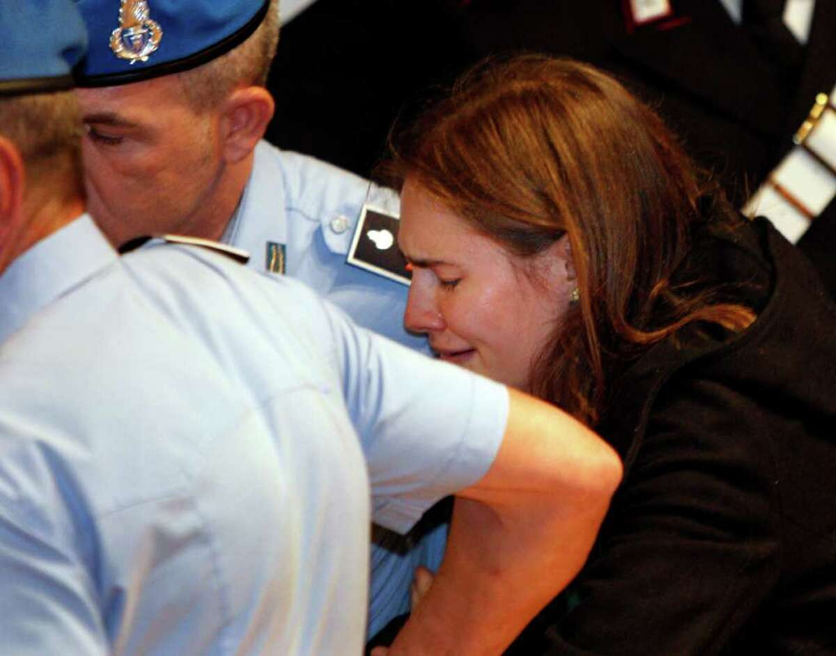 Amanda Knox breaks in tears as she is taken away after hearing the verdict that overturns her conviction and acquits her of murdering her British roommate Meredith Kercher, at the Perugia court, central Italy, Monday, Oct. 3, 2011. Italian appeals court threw out Amanda Knox's murder conviction Monday and ordered the young American freed after nearly four years in prison for the death of her British roommate. Knox collapsed in tears after the verdict overturning her 2009 conviction was read out. Her co-defendant, Italian Raffaele Sollecito, also was cleared of killing 21-year-old Meredith Kercher in 2007.(AP Photo/Pier Paolo Cito)