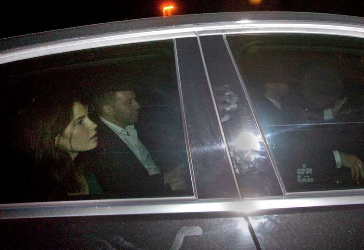 Amanda Knox, left, leaves the Perugia court on a car following the verdict that overturns her conviction and acquits her of murdering her British roomate Meredith Kercher, Monday Oct. 3, 2011. An Italian appeals court has thrown out Amanda Knox's murder conviction and ordered the young American freed after nearly four years in prison for the death of her British roommate. Knox collapsed in tears after the verdict was read out Monday. Her co-defendant, Raffaele Sollecito, also was cleared of killing 21-year-old Meredith Kercher in 2007.