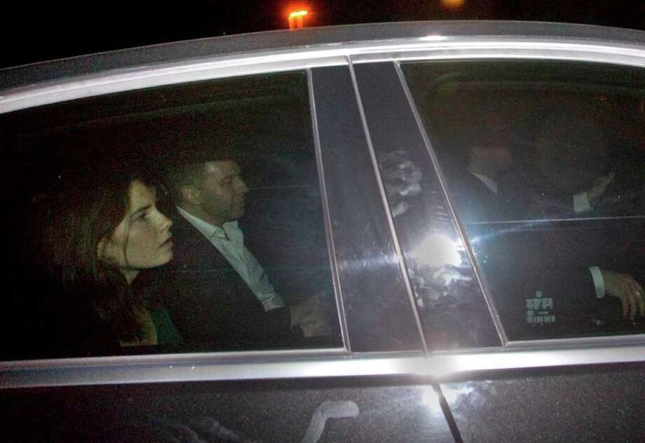 Amanda Knox, left, leaves the Perugia court on a car following the verdict that overturns her conviction and acquits her of murdering her British roomate Meredith Kercher, Monday Oct. 3, 2011. An Italian appeals court has thrown out Amanda Knox's murder conviction and ordered the young American freed after nearly four years in prison for the death of her British roommate. Knox collapsed in tears after the verdict was read out Monday. Her co-defendant, Raffaele Sollecito, also was cleared of killing 21-year-old Meredith Kercher in 2007. Photo: Angelo Carconi, AP / AP