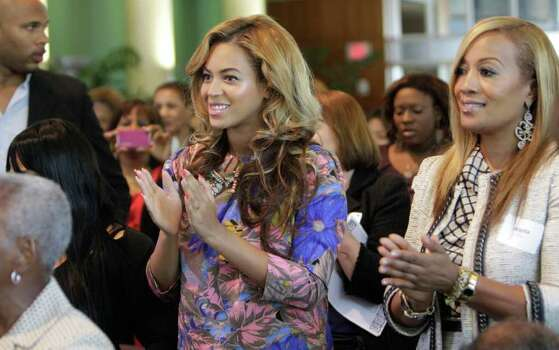 Beyonce Knowles and a family friend applaud Tina Knowles. Photo: Melissa Phillip / © 2011 Houston Chronicle