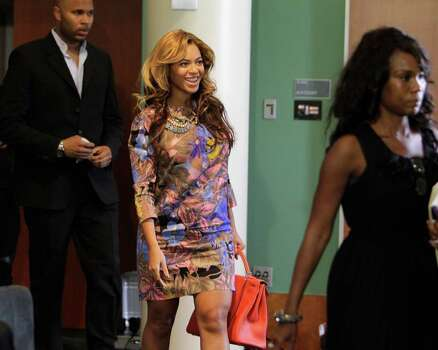 Beyonce Knowles, accompanied by her body guard and publicist, at University of Houston MD Anderson Library. Photo: Melissa Phillip / © 2011 Houston Chronicle