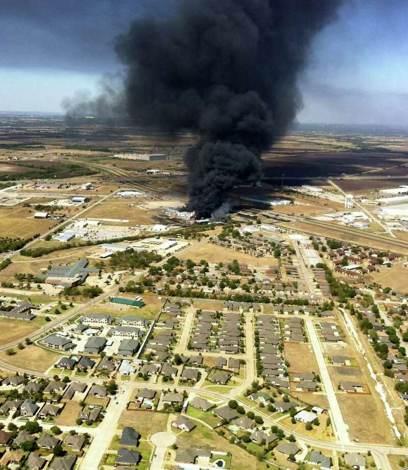 A plume of smoke rises from the Magnablend chemical processing plant,  in Waxahachie, Texas, Monday, Oct. 3, 2011. Flames triggered several explosions as burning liquid spread along the ground and under a firetruck at the plant, causing it to explode. Employees who were inside a warehouse at the plant evacuated safely when the fire broke out. Photo: Lara Solt, Associated Press / The Dallas Morning News