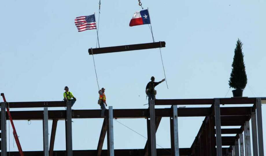 "Workers place the final beam during the ""topping out"" ceremony of the library for President George W. Bush at SMU in  Dallas,  Monday, Oct. 3, 2011.  (AP Photo/LM Otero) Photo: LM Otero, Associated Press / AP"