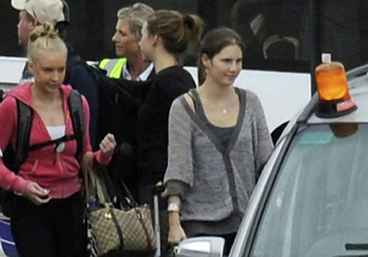 Amanda Knox, right, arrives from Rome with family members at Heathrow Airport London, Tuesday. Amanda Knox headed home to the United States a free woman Tuesday, after an Italian appeals court dramatically overturned the American student's conviction of sexually assaulting and brutally slaying her British roommate. (AP Photo/Pool)