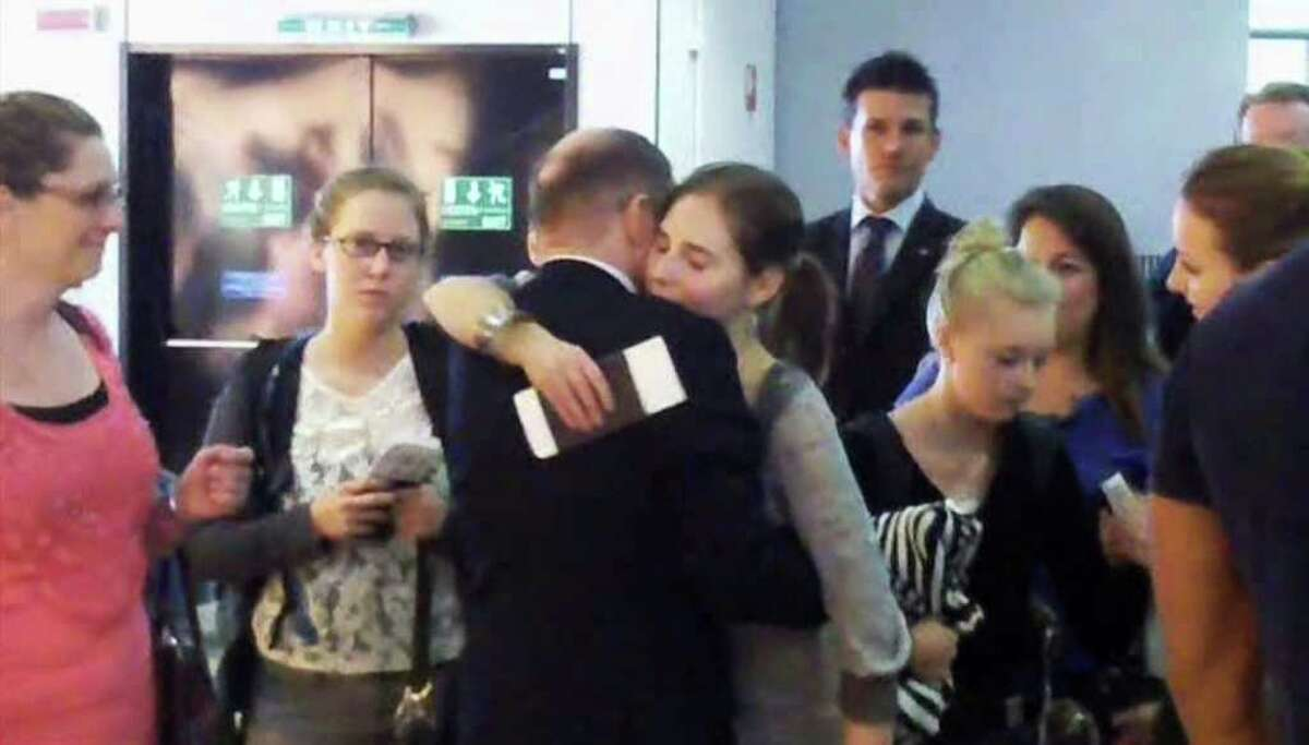 In this image made from amateur video accessed by APTN, Amanda Knox, fourth from right, embraces an unidentified person at Rome's Leonardo da Vinci airport, Tuesday. Amanda Knox was leaving Italy a free woman Tuesday, the morning after an Italian appeals court dramatically overturned the American student's conviction of sexually assaulting and brutally slaying her British roommate. The Italy-US Foundation, which has championed Knox's cause, said the American was at Leonardo da Vinci airport in Rome boarding a flight to London, where she will catch a connecting flight to the United States. (AP Photo)