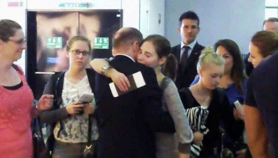 In this image made from amateur video accessed by APTN, Amanda Knox, fourth from right, embraces an unidentified person at Rome's Leonardo da Vinci airport, Tuesday. Amanda Knox was leaving Italy a free woman Tuesday, the morning after an Italian appeals court dramatically overturned the American student's conviction of sexually assaulting and brutally slaying her British roommate. The Italy-US Foundation, which has championed Knox's cause, said the American was at Leonardo da Vinci airport in Rome boarding a flight to London, where she will catch a connecting flight to the United States. (AP Photo) Photo: Anonymous, ASSOCIATED PRESS / AP2011