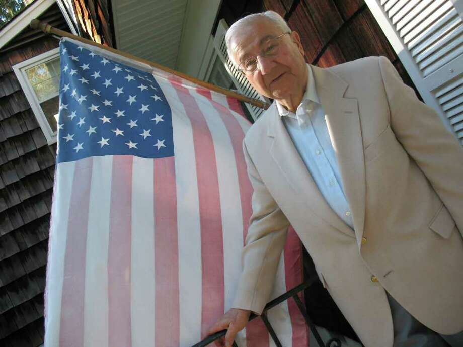 "Emil ""Bennie"" Benvenuto stands by the flag at his North Mianus home in this 2010 file photo. Benvenuto, an anchor of the Greenwich GOP who was blackballed by his party for his support of Lowell Weicker Jr., died early Tuesday morning. He was 80. Benvenuto had been suffering from prostate cancer, according to friends. Elected to the 151st District in the state House of Representatives in 1976, serving six terms, Benvenuto then captured the 36th District in the Senate. He served for two years before a split among local Republicans saw him lose to William Nickerson in 1990. Photo: File Photo / Greenwich Time File Photo"