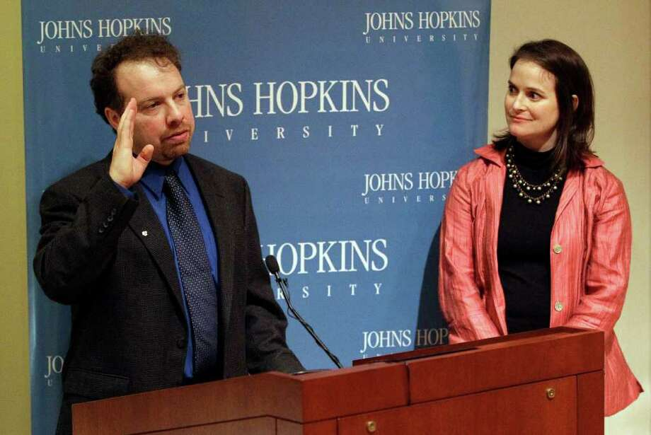 Dr. Adam Riess, left, speaks alongside his wife Nancy, a Greenwich native, at a news conference to acknowledge his Nobel Prize in Physics at Johns Hopkins University in Baltimore, Tuesday, Oct. 4, 2011. Riess shared the prize with Saul Perlmutter, an astrophysicist at the University of California, Berkeley, and Brian Schmidt of the Australian National University, for their contributions to the discovery that the universe's expansion is accelerating. (AP Photo/Patrick Semansky) Photo: Patrick Semansky, Associated Press / AP