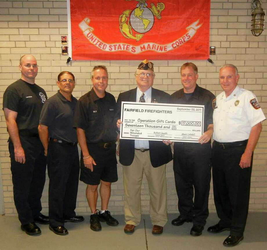 A ceremonial presentation of $17,000 from this year's Fairfield Road Races was presented by Fairfield firefighters recently to Operation Gift Cards, which helps wounded soldiers. From left are: Firefighters Lieut. William Tuttle, Alan Menillo, Rick Kazzi, Operation Gift Cards official Tim Kelly, Fairfield Firefighters Association Local 1426 President Robert Smith Jr. and Chief Richard Felner. Photo: Contributed Photo / Fairfield Citizen contributed