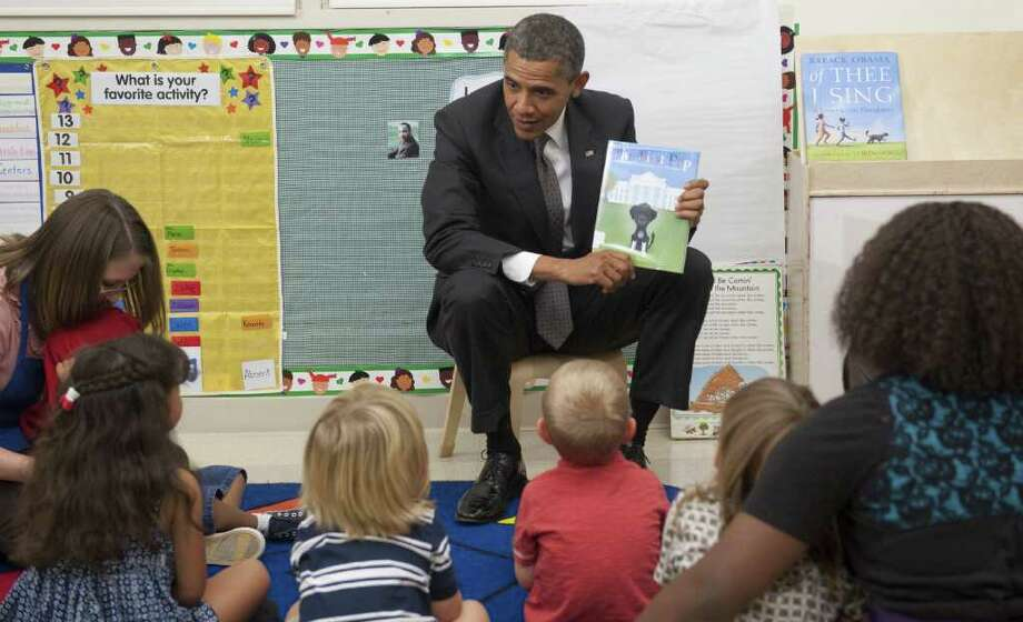 US President Barack Obama holds up a book about his dog, Bo, as he speaks with 3 to 5 year old children as he tours the Children's Laboratory School at Eastfield College in Mesquite, Texas, October 4, 2011, prior to speaking about the American Jobs Act and rebuilding American schools. Photo: SAUL LOEB, Getty / AFP