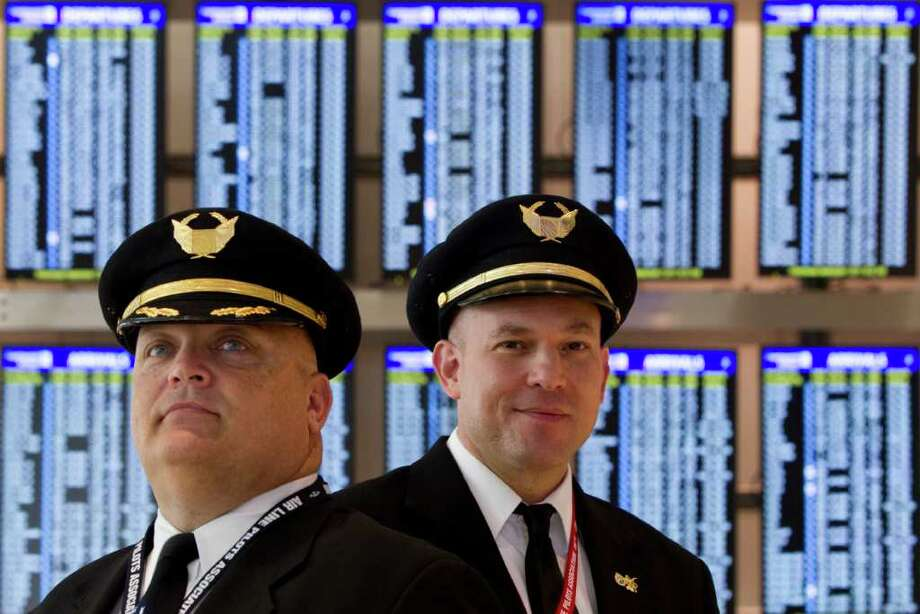 BRETT COOMER : CHRONICLE ROUTINE: Pilots Capt. Mike Jones, left, and First Officer Justin Maximov say life for them is nothing like that portrayed in Pan Am. For example, Maximov says he almost never travels on his day off because it's much harder now to find a free seat. Photo: Brett Coomer / © 2011 Houston Chronicle