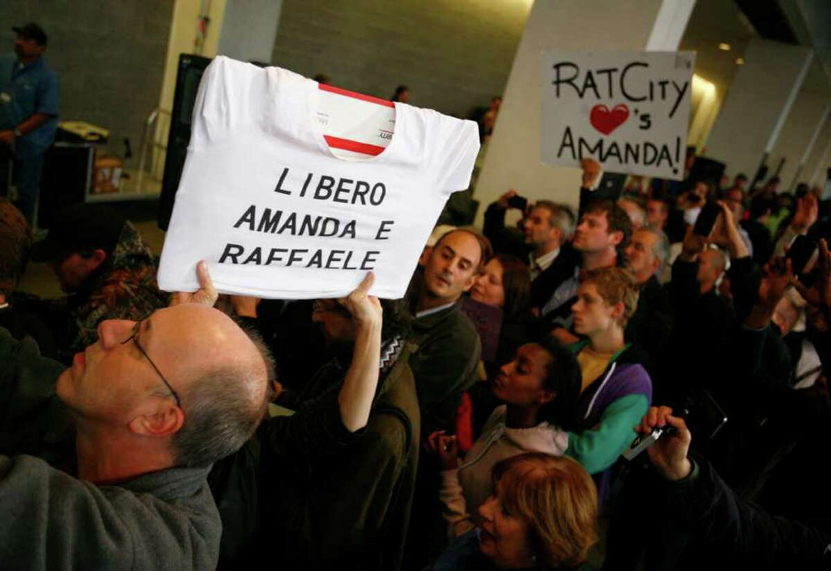 Supporters hold up signs as Amanda Knox returns to the United States after her Italian murder conviction was overturned.