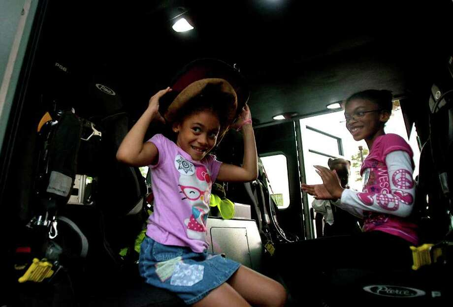 Brianna Mims, 7, tries on a fire fighter's helmet while her sister Mykayla Mims, 9, watches during the National Night Out in the neighborhood of Fall Creek Tuesday, Oct. 4, 2011, in Houston. Photo: Cody Duty, Houston Chronicle / © 2011 Houston Chronicle