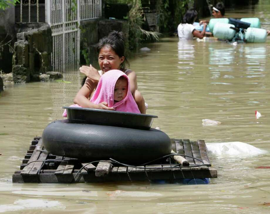 Residents use an improvised raft for transport as floodwaters continue to inundate Calumpit township, Bulacan province, north of Manila, Philippines Monday Oct. 3, 2011. Floodwaters slowly receded Monday in many parts of the northern Philippines after two typhoons that killed nearly 60 people, amid appeals for more boats to bring food and water to residents refusing to abandon inundated homes. Photo: BULLIT MARQUEZ, Associated Press / AP