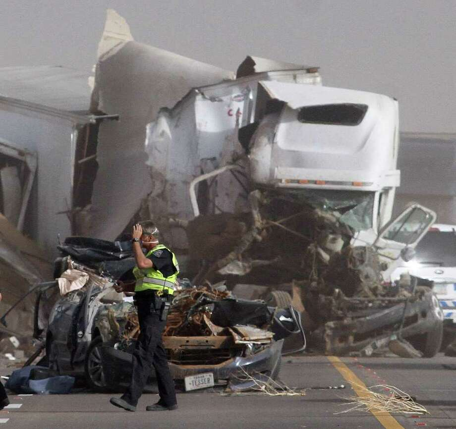 An Arizona Department of Public Safety Officer walks in front of two vehicles that were involved in two crashes that involved 16 vehicles on Interstate 10 near Picacho Peak, about midway between Phoenix and Tucson, Tuesday, Oct. 4, 2011. Photo: Darryl Webb, Associated Press / FR170361 AP