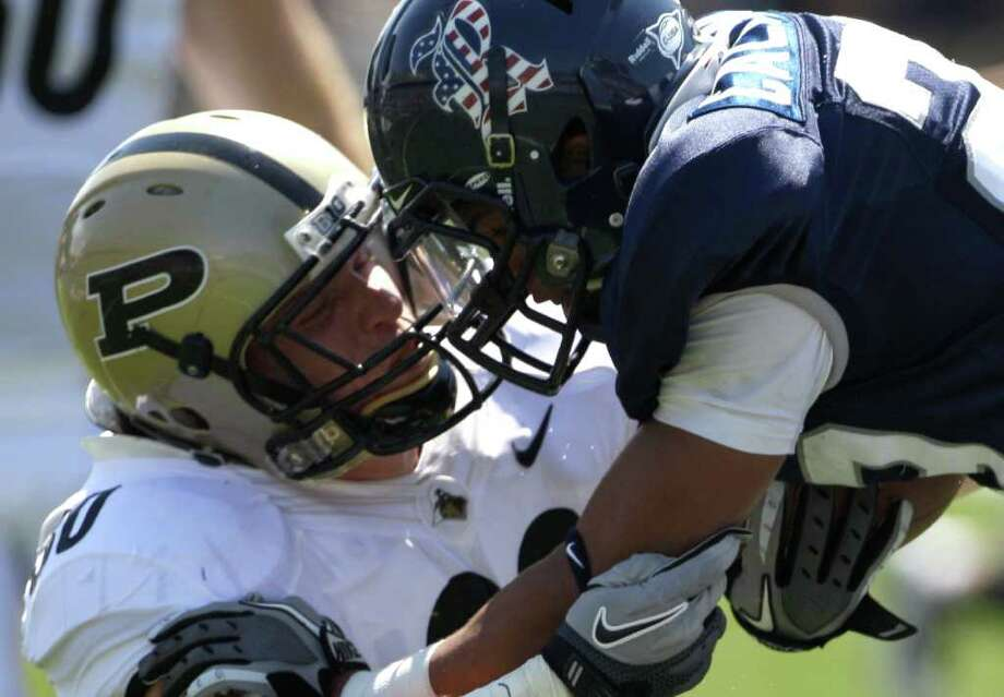 """Known as """"Ballhawk"""" for his knack for interceptions, Rice's Bryce Callahan, right, carries it in more conventional fashion on a punt return against Purdue. Photo: David J. Phillip / AP"""