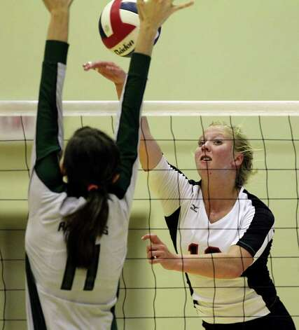 Churchill's Kelsey Raglin tips a ball by Reagan's Ashlie Reasor as the Rattlers defeat Churchill in three games Tuesday, Oct. 4, 2011 at Littleton Gym. Photo: Tom Reel/treel@express-news.net / © 2011 San Antonio Express-News