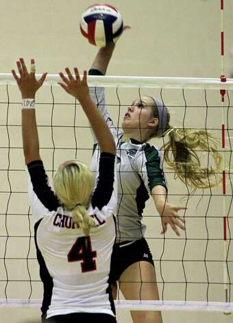 Reagan's Bailey Shurbet goes for a kill over Churchill's Jordan Holub (4) as the Rattlers win in three games Tuesday, Oct. 4, 2011 at Littleton Gym. Photo: Tom Reel/treel@express-news.net / treel@express-news.net