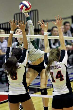 Reagan's Dayna Kramer takes a shot over Churchill's Tori Guerra (3) and Audrey Sanders as the Rattlers win in three games Tuesday, Oct. 4, 2011 at Littleton Gym. Photo: Tom Reel/treel@express-news.net / © 2011 San Antonio Express-News