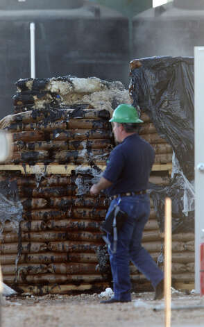 A TECQ worker walks past smoldering bags. Photo: Jerry Lara/glara@express-news.net / SAN ANTONIO EXPRESS-NEWS