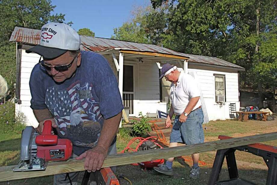 MAKING IT BETTER: Mike Schriver of the Fellowship of Cinco Ranch cuts boards as he works on a team with Gene Cover of Cornerstone Evangelistic Presbyterian Church. Photo: Suzanne Rehak